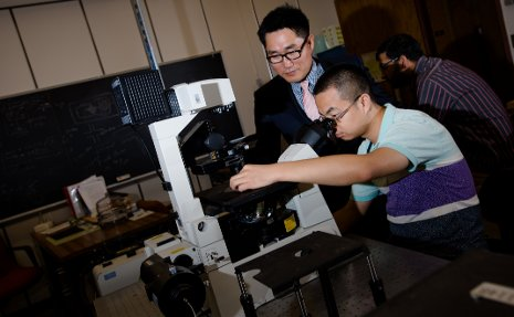 C.K. Choi, left, and PhD candidate Shuo Wang    examine flow fields in a micro-channel, using the Nikon TI series inverted microscope.