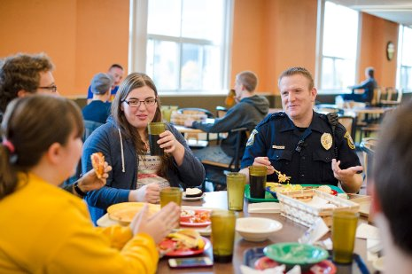 Officer Reid DeVoge sits down for dinner with residents in Wadsworth Hall as part of the Residential Officer Program.