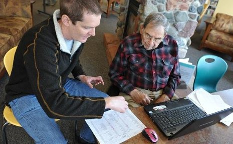 Chuck Wallace, at left, helps Bob Veeser use his computer.