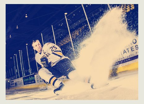 Hockey player spraying snow while stopping on the ice.