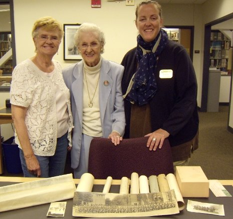 Ellen Raymond, center, donated her father-in-law's memorabilia from nearly a century ago to the Michigan Tech Archives at the suggestion of her friend, Sharon Eklund, left. Archivist Beth Russell called the gifts