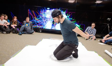 Orrico kneels on a large piece of paper, creating a piece of art while his movements are tracked by Tech's Mind Music Machine Lab researchers.