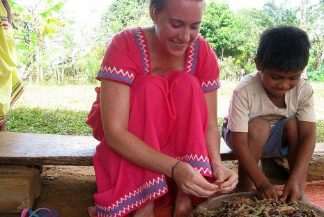 Peace Corps Masters International graduate student Erica Jones helps a village boy shuck beans in Panama.
