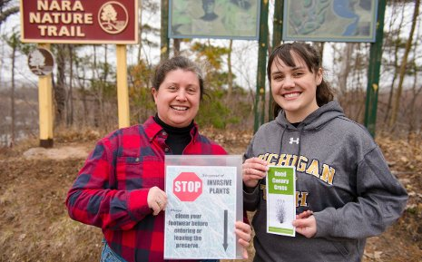 Meral Jackson, left, and Krysten Cooper, with a sample of the sign and brochure that Krysten designed to prevent the spread of reed canary grass at Nara Nature Park. The actual signs will be larger, brighter, sturdier, and mounted on posts.