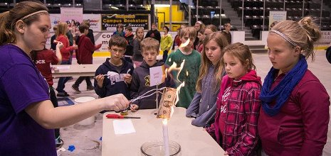A high school student trained by Mind Trekkers shows rapt elementary school children that money really doesn't burn--if you soak it in an alcohol-water solution before setting it afire.