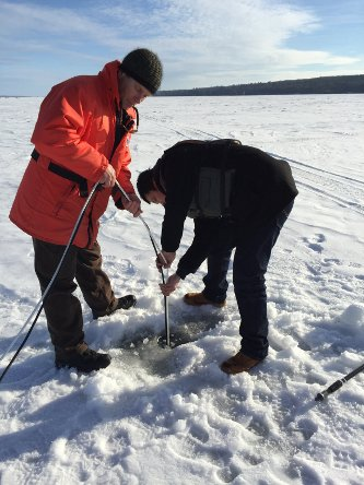 Researchers feeding cords through a hole in the ice.