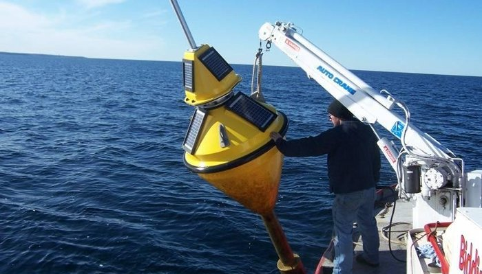 Deploying the buoy to monitor water conditions in the Straits of Mackinac.