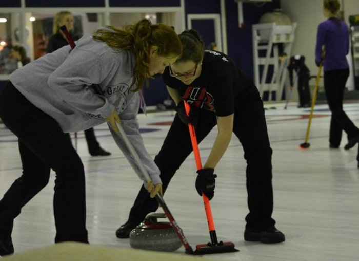 Alexis Schroeder (right) and a teammate sweep the ice to help direct the stone.