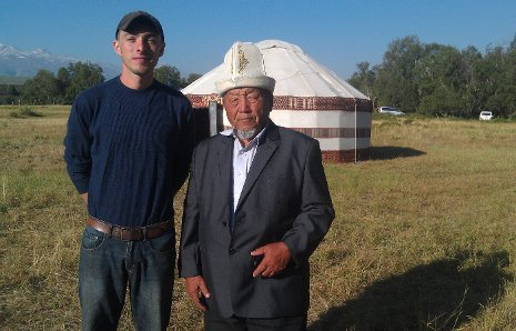 Cole Bedford, left, with a community member wearing a kalpak, traditional Kyrgyz headwear, standing in front of a Kyrgyz yurt.