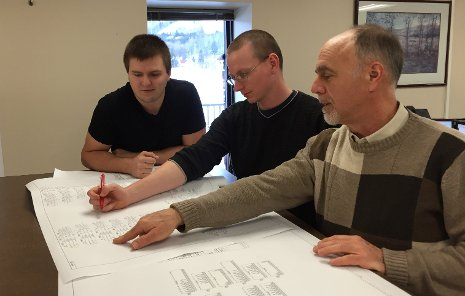 From the left,  Troy Johnston and Bob Elsey, interns at Systems Control's Houghton office, work with Tech alumnus John Zipp, senior protection and control engineer, on a schematic for a bus differential panel to be incorporated into an electrical transmission substation control house.