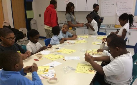 Michigan Tech student Rebecca Spencer, standing center in grey polo shirt, is seen working with Detroit school children in March of 2014. Once again this year members of Michigan Tech's chapter of the National Society of Black Engineers will spend spring break working with Detroit youth.