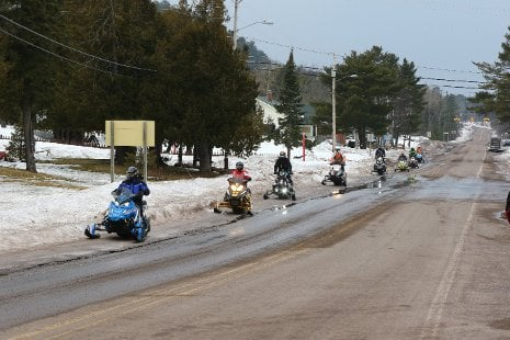 Snowmobiles driving along the side of a road.