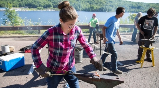 Summer Youth Programs student learning about what blacksmiths do.
