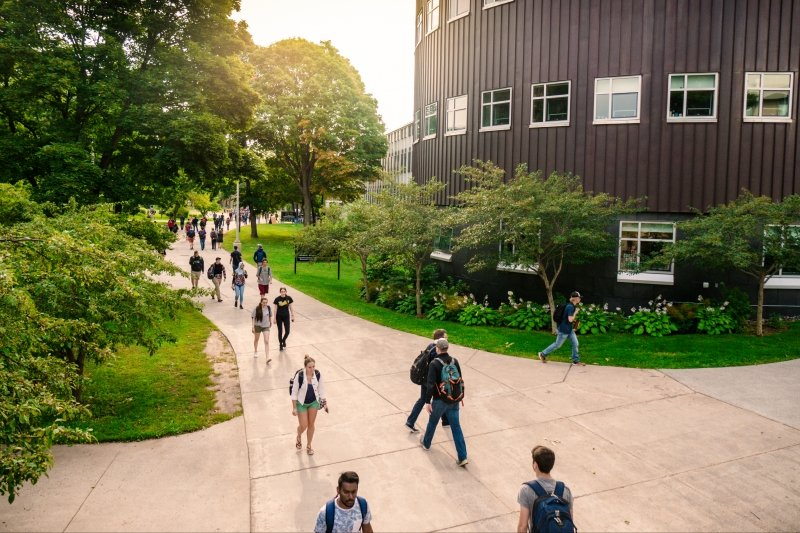 Students walking on campus by Rehki building