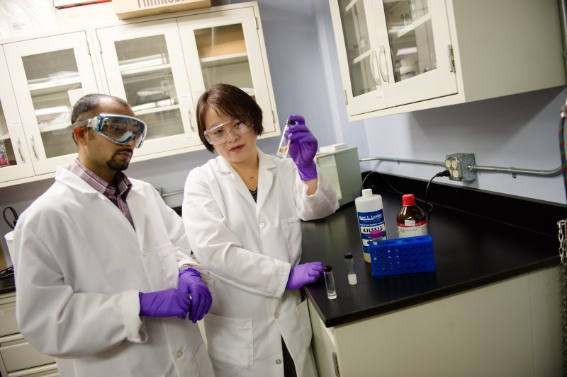 Two researchers in a lab looking at a vial of solution one researcher is holding up.