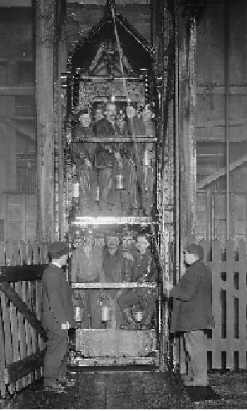 Twelve plus miners in a wooden cart on a pully system