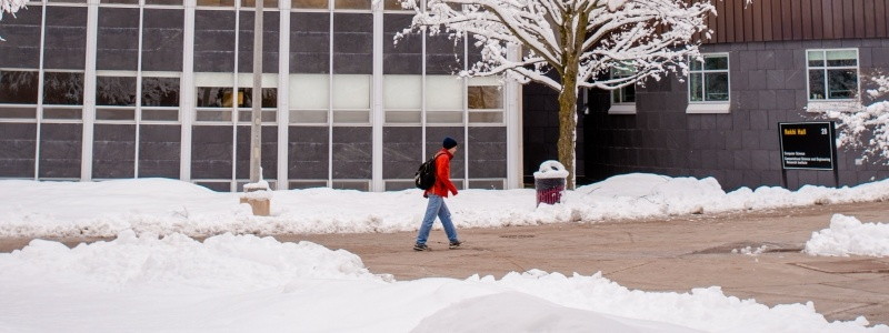 Student walking between Rekhi and Fisher Hall in winter.