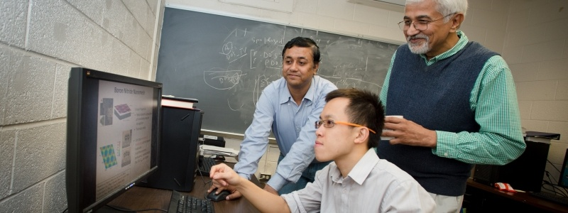 Department Chair, Ravi Pandey, looks on as two graduate students explain while sitting at a computer