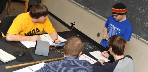 Four students work on completing a Physics lab report.