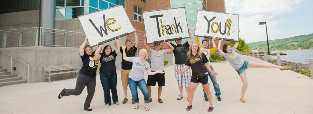 "A group of students in unique poses holding three signs with signatures; the signs have the words ""We Thank You"" with one word per sign."