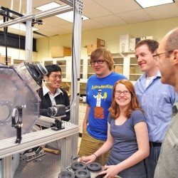 Four Grad students talking with faculty in a physics lab with small cloud chamber