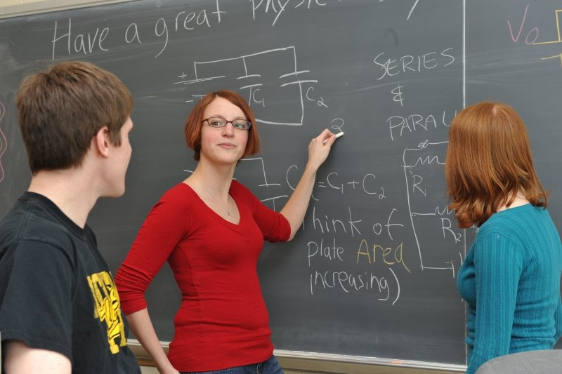 One student standing at a blackboard with chalk instructing two students who are listening