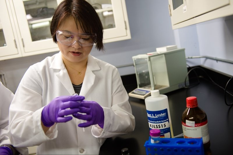 Student in Yoke Khin Yap's lab hold a vial of solution