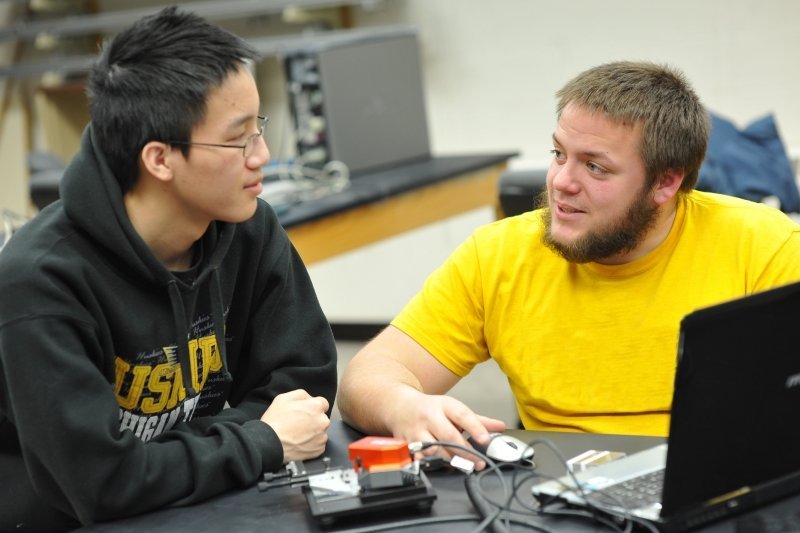 Two physics students in from of computer discussing