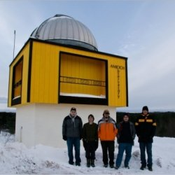 Students stand outside of observatory in winter