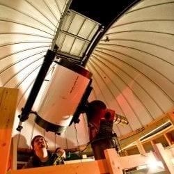 Student sits and looks through the telescope