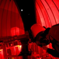 Student stands and looks through the telescope with lights dimmed.