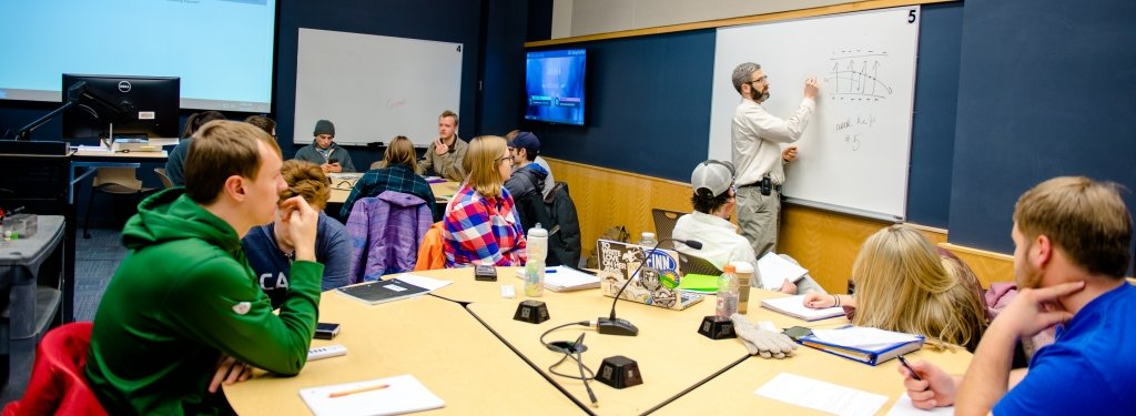 Faculty standing in front of a white board writing in front of circle tables of students looking on.