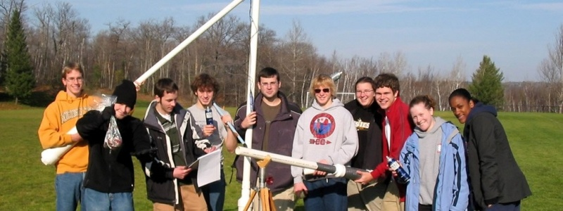 Ten students in the field posing for a photograph with potato guns after measuring the physics after potatoes are projected.