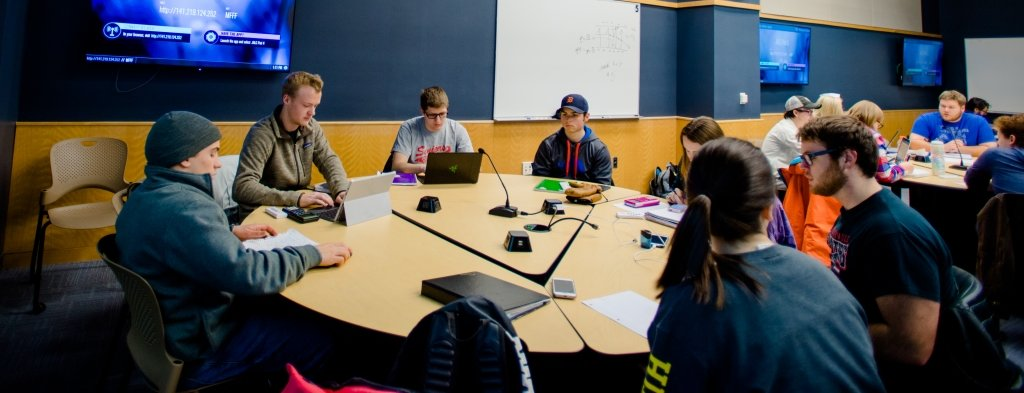 A classroom with students at round tables.