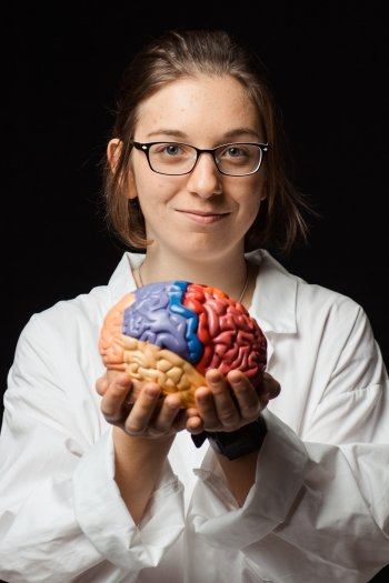 Pre-health student in lab coat holding a model of a brain