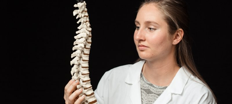 Student in a lab coat looking at a model of a spine.