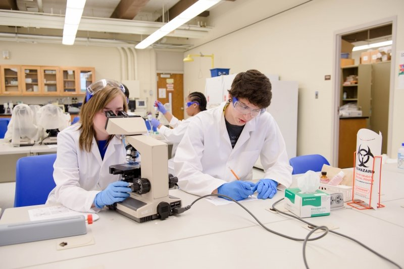 Three medical students, one in the background taking measurements, one in the forefront looking through a microscope, and a third student writing down measurements