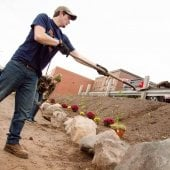 Student shoveling dirt into a flower bed