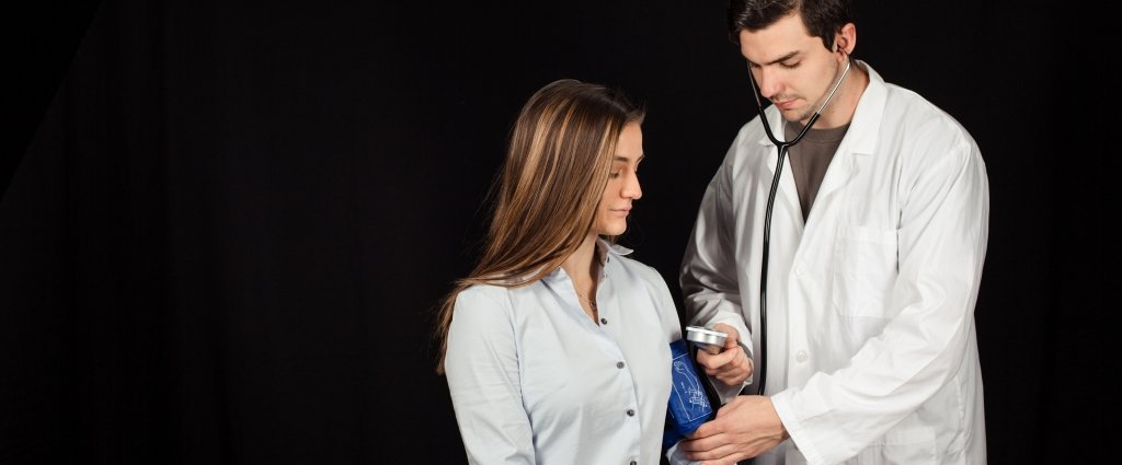 A pre-medical student in lab coat taking the blood pressure of another student