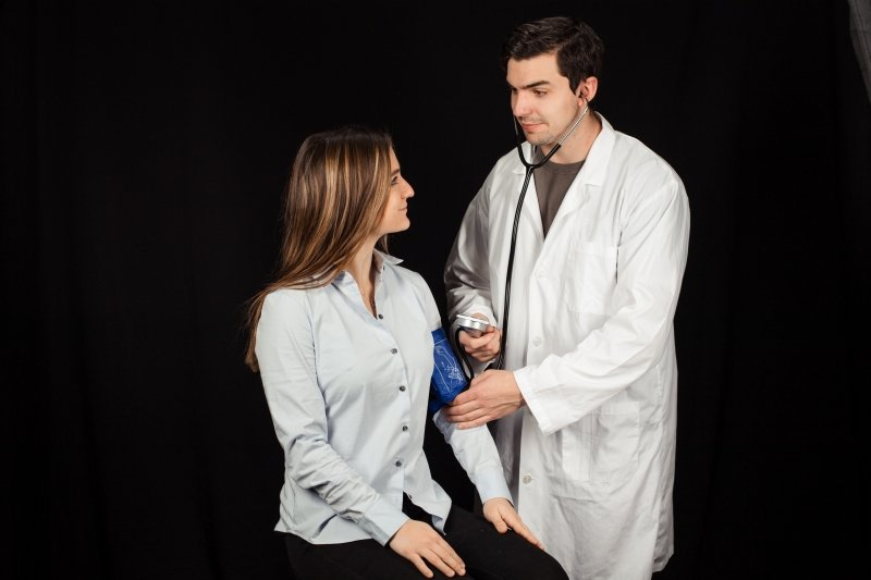 Female physician assistant pulling on a medical sleeve onto an older gentleman while he sits in a chair