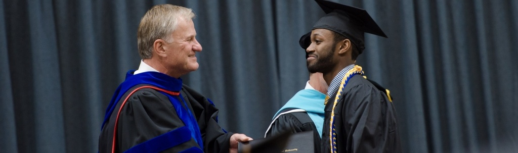 President Mroz shaking hands with a graduate