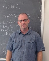 portrait photograph of David in front of a chalk board with equations