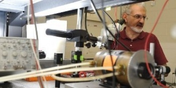 Miguel Levy, professor, stands behind nano equipment making adjustments