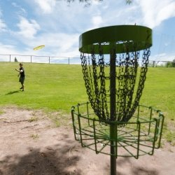 Student throwing a disc at a disc golf basket on the Michigan Tech course.