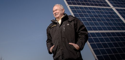 A man stands in front of a solar panel array.