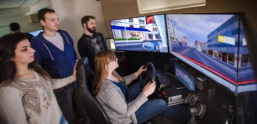 A group of researchers observe a woman using a driving simulator.