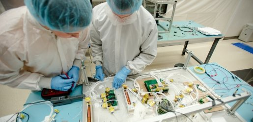 Two individuals working on aerospace/satellite components