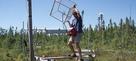 A man carries a large sensor setup through the woods.