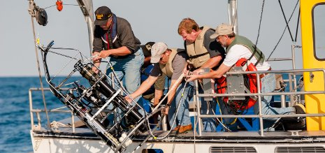 Researchers drop an underwater probe off of a boat.