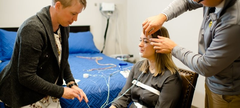Researchers applying sleep monitoring equipment to participant